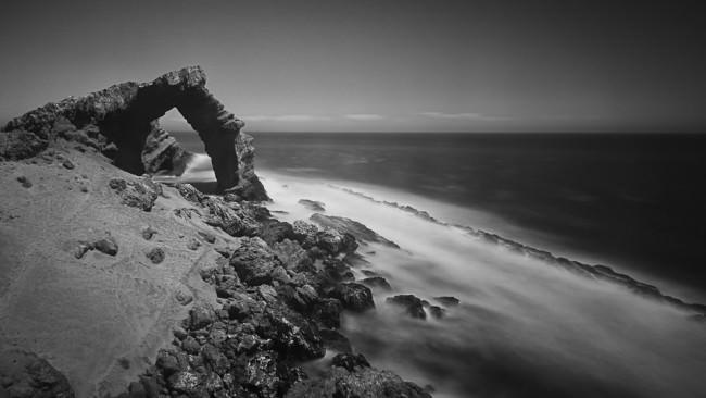 Langzeitbelichtung Bogenfels in der Wüste am Meer.