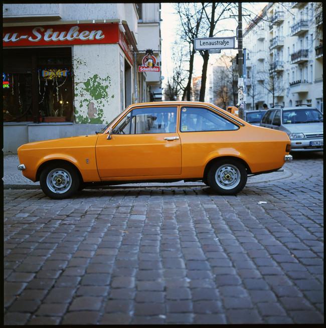 Ein altes orangenes Auto in der Stadt.