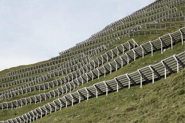 Lawinenschutzbauten an einem grünen Berghang.