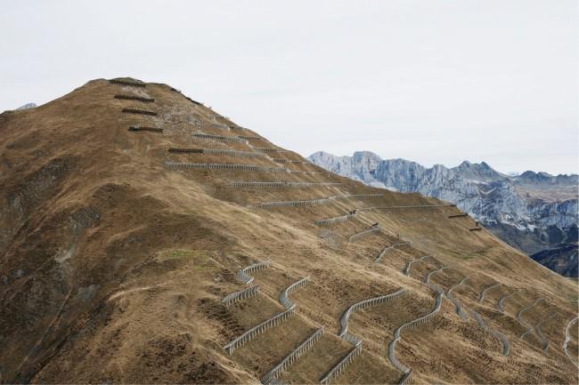 Lawinenschutzbauten an einem kahlen Berghang, dahinter weitere Berge.