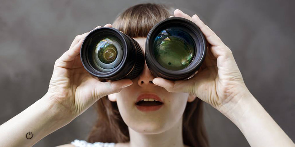 Eine Frau mit zwei Objektiven als Fernglas