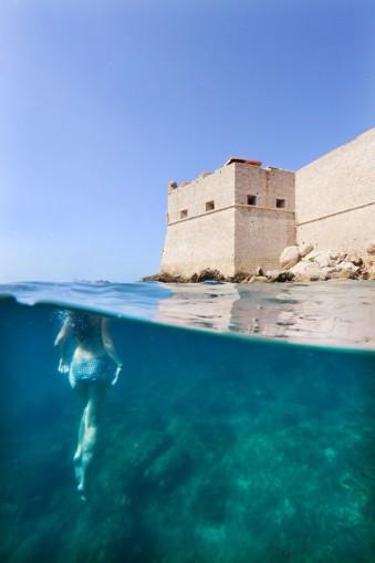 Eine Taucherin vor einer Festung