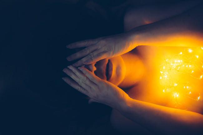 Eine Frau hält sich die Hände vor das Gesicht. Auf ihrer Brust brennt eine Lichterkette.