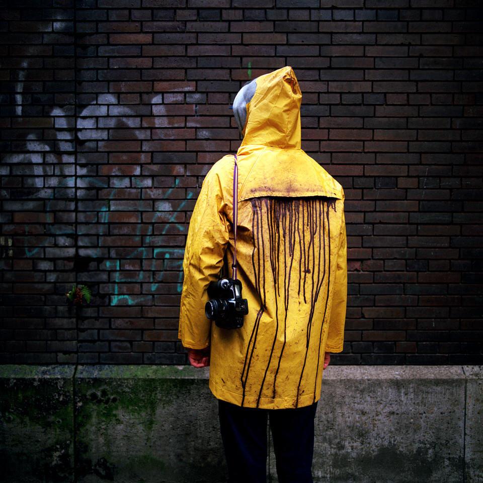 Eine Person mit gelber Regenjacke aus der schwarze Farbe tropft mit dem Rücken zur Kamera.