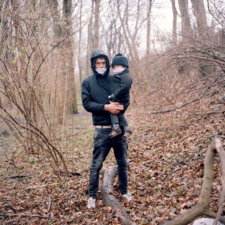 Ein Mann mit Kind auf dem Arm. Beide tragen Mundschutzmasken.