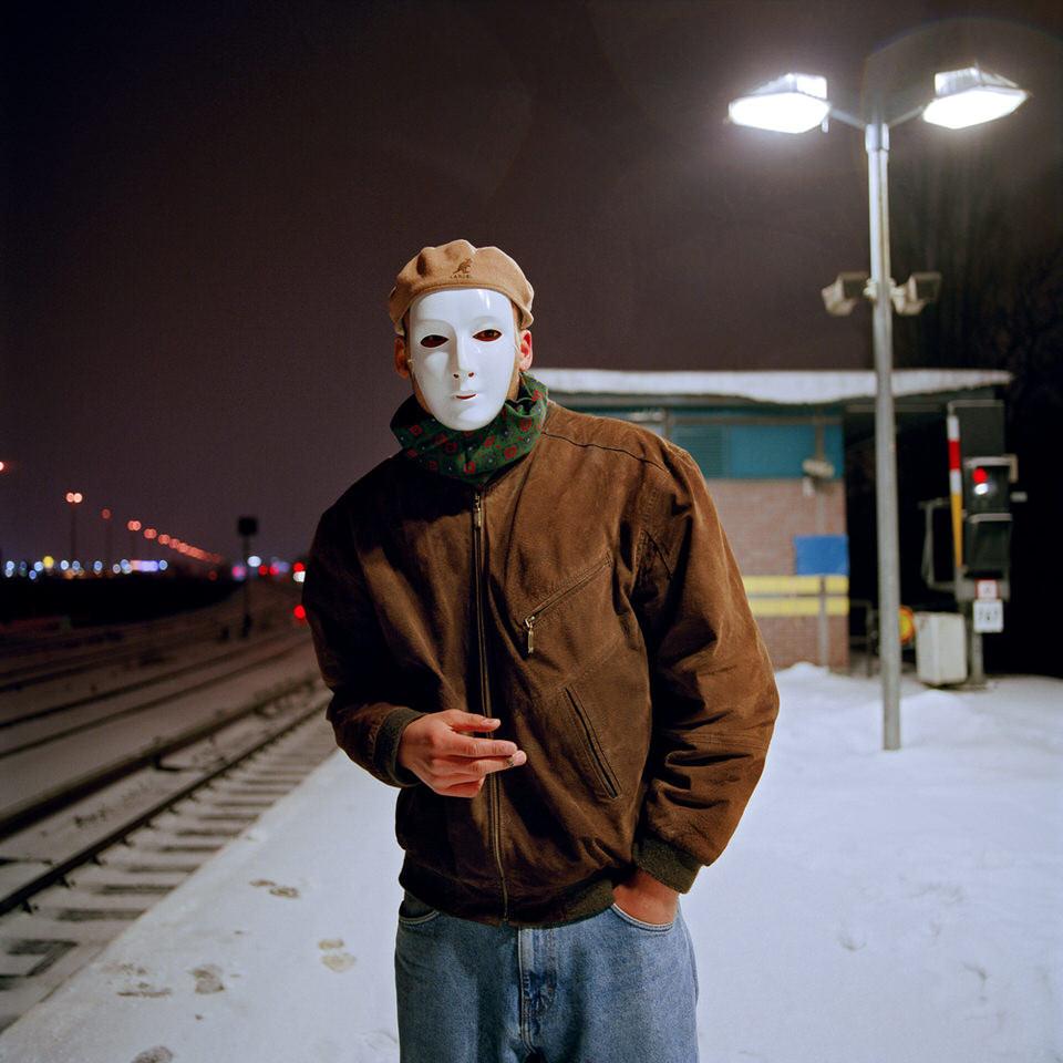 Ein Mann mit weißer Maske an einem Bahnhof