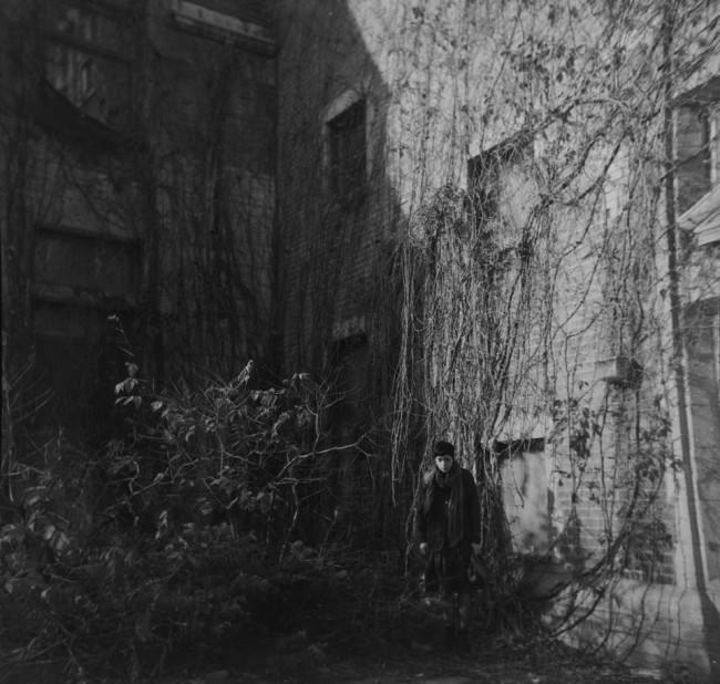 Frau in einem überwucherten Innenhof, umgeben von mit Efeu bewachsenen Hauswänden.
