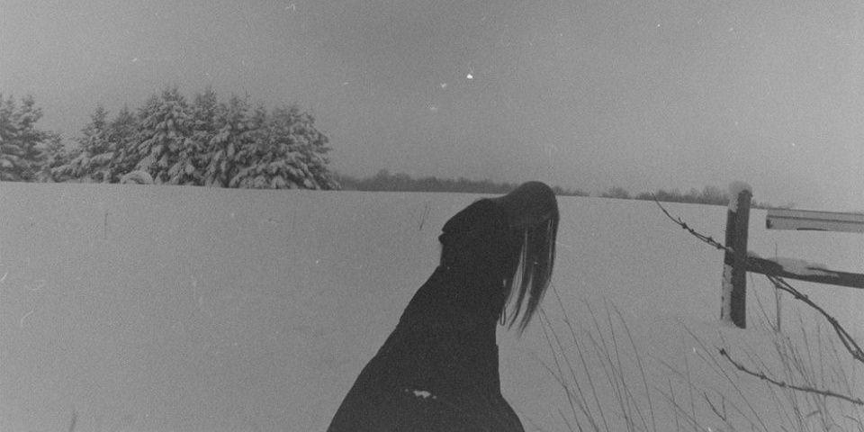Gebeugt gehende Frau vor einer Schneelandschaft.