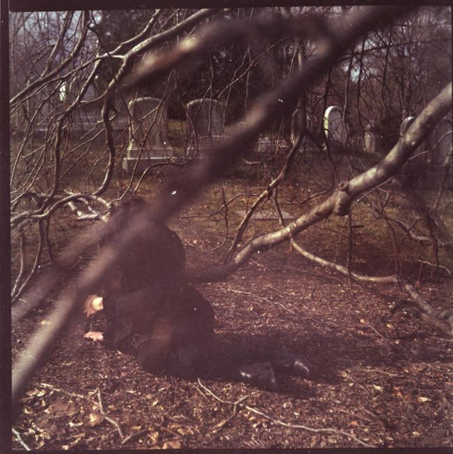 Eine Person versteckt sich auf einem Friedhof hinter einem Ast.