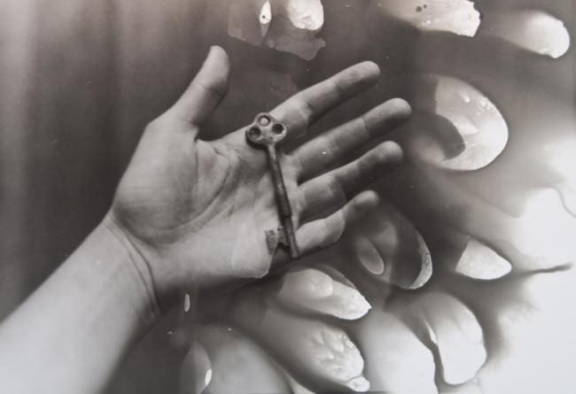 Ein Schlüssel liegt in einer offenen Handfläche mit Bildfehlern.