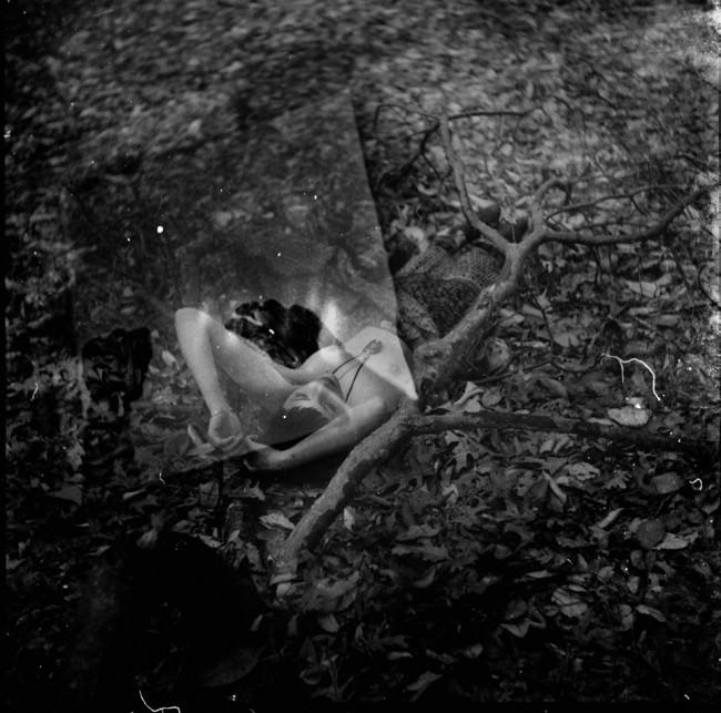 Eine Frau mit nacktem Oberkörper liegt neben einem Ast im Laub.