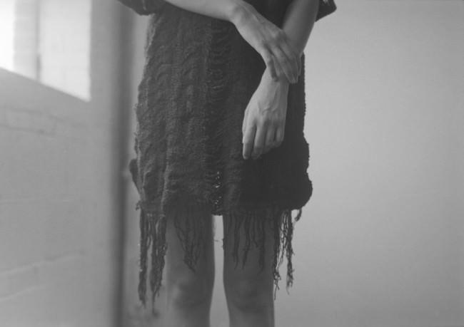 Arme und Beine einer stehenden Frau mit zotteligem, übergroßem Pullover.