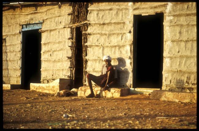 Ein Mann sitzt vor einem Haus.