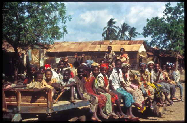 Männer und Frauen sitzen auf einem Laster.