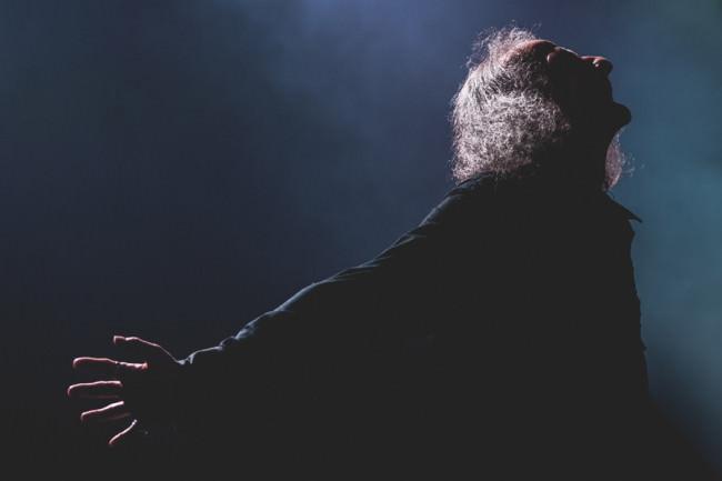 Älterer Mann im Dunkeln, leicht von hinten beleuchtet.