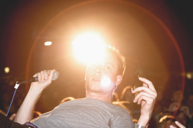 Sänger schaut in die Kamera, Licht direkt hinter seinem Kopf.