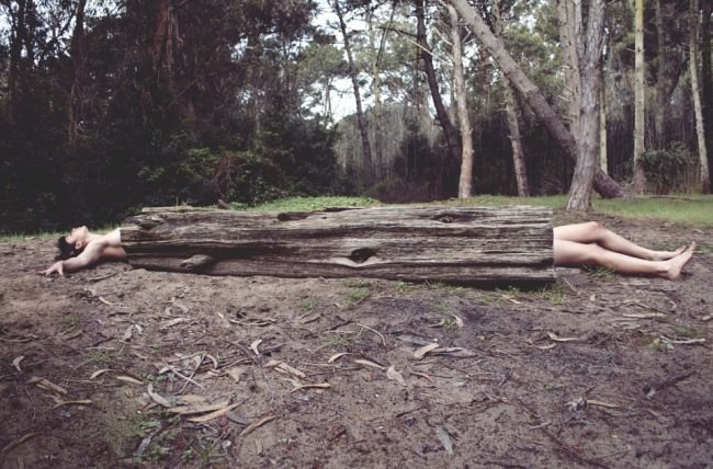 Ein Oberkörper und nackte Beine schauen auf beiden Seiten eines hohlen Baumstammes hervor.