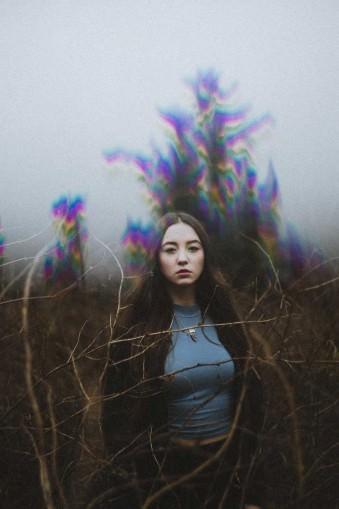 Eine Frau vor einem Baum mit surrealen Farben