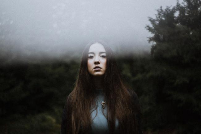 Eine Frau im Wald mit einem Lichtreflex
