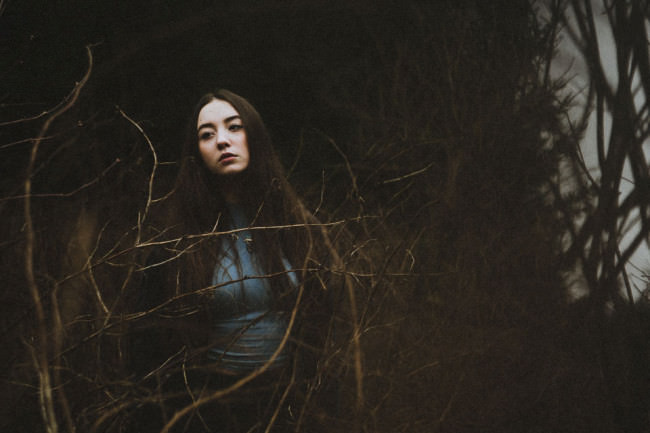 Eine Frau zwischen Gestrüpp im Wald