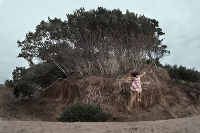 Eine Frau im rosa Kleid springt von einem Hügel mit Bäumen.