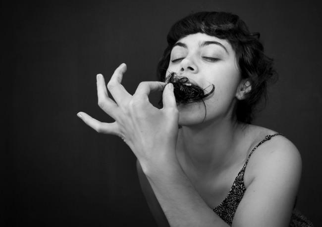 Eine Frau mit geschlossenen Augen isst Haare.