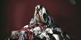 Eine Frau liegt unter einem Wäscheberg vergraben.
