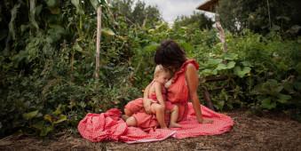Eine Frau stillt ein Kind in der Natur