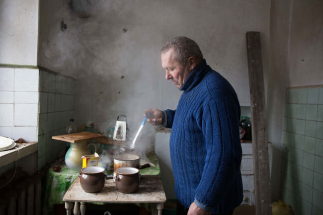 Ein Mann kocht vor einer blanken Wand.