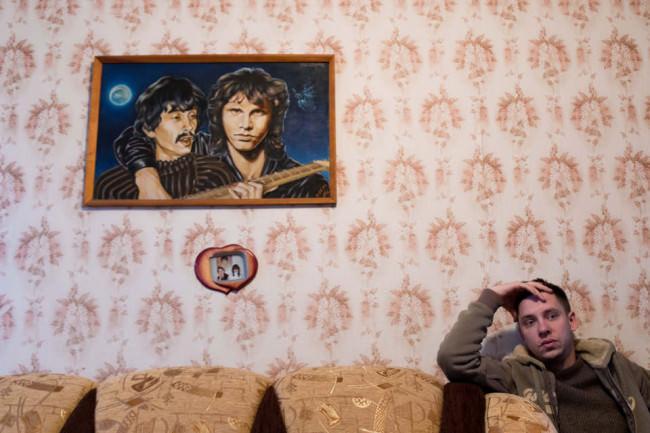 Eine Person sitzt auf einem Sofa unter einem Bild