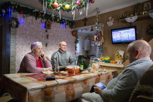 Drei Personen sitzen um einen Tisch in einem dekorierten Raum