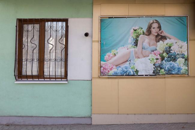 Ein Plakat hängt an einer Hauswand neben einem Fenster