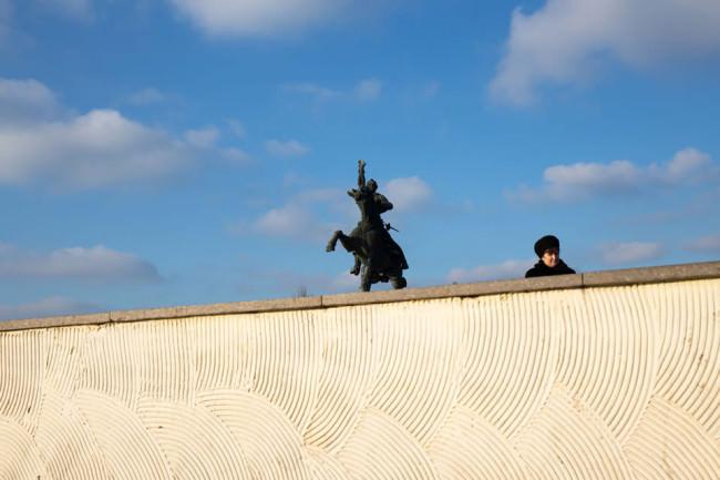 Hinter einer Mauer schauen eine Person und eine Statue hervor