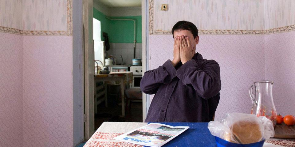 Eine Person sitzt an einem Tisch und hält sich das Gesicht zu