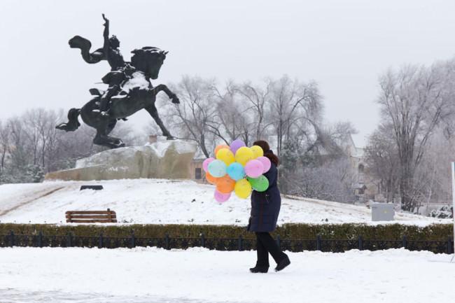 Eine Person trägt Luftballons vor einer Statute