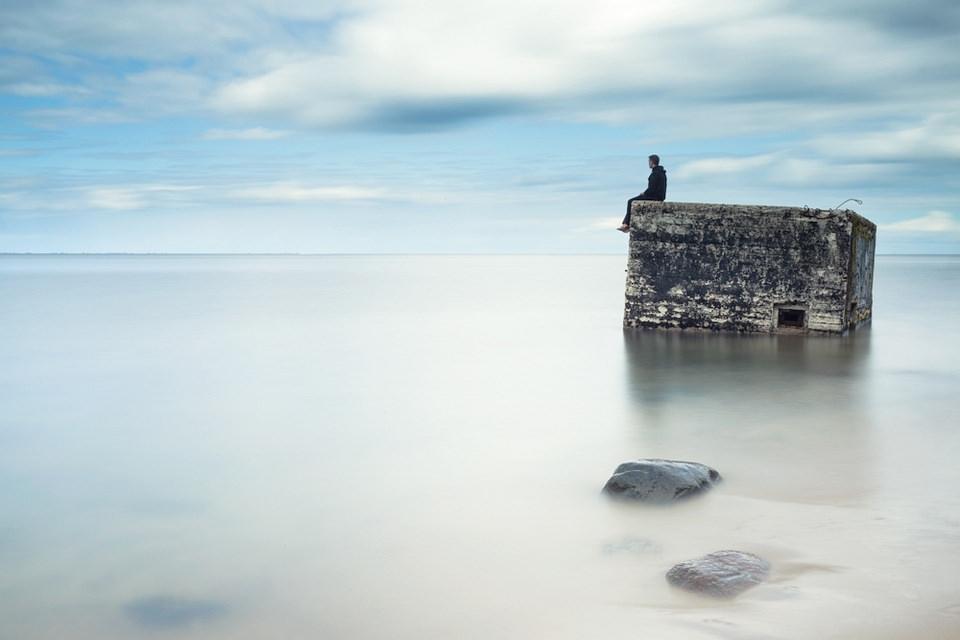 Eine Person sitzt auf dem Rand eines Bunkers, der aus der Meeresoberfläche ragt.