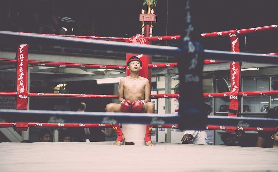 Junger Boxer sitzt in einer Ecke im Ring.