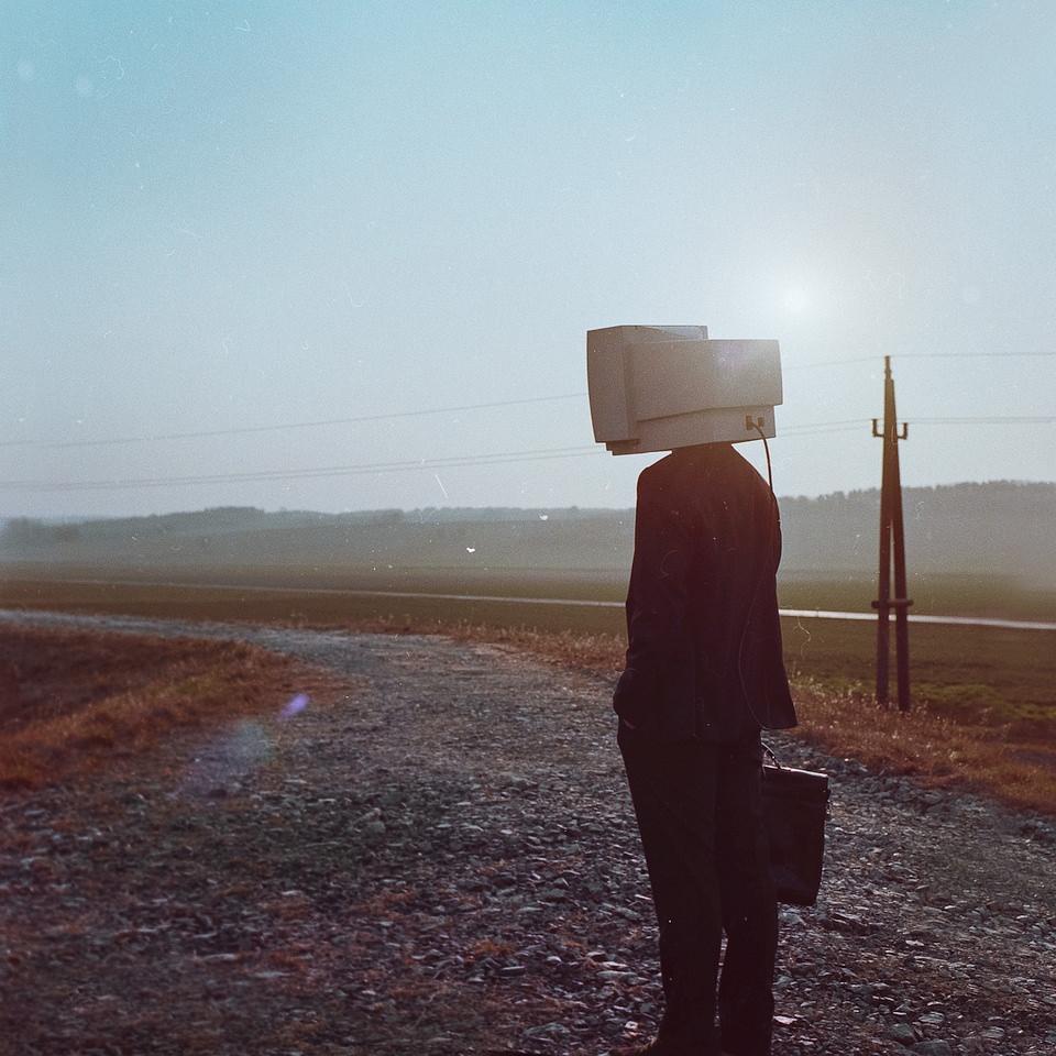Mann im Anzug mit Aktenkoffer und Computerbildschirm statt Kopf steht auf einer ländlichen Straße.