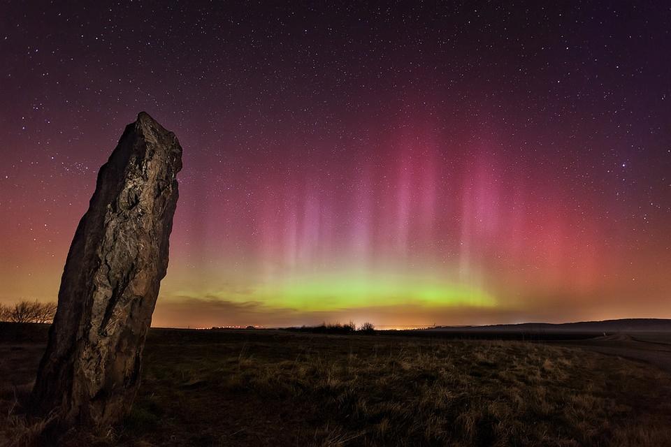 Ein rosagelber Himmel mit Nordlichtern, hinter einem aufragenden Felsen.