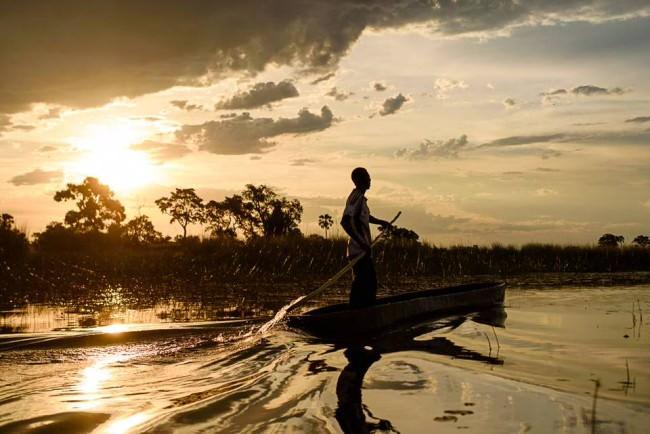 Ein Mann in einem kleinen Boot im Gegenlicht