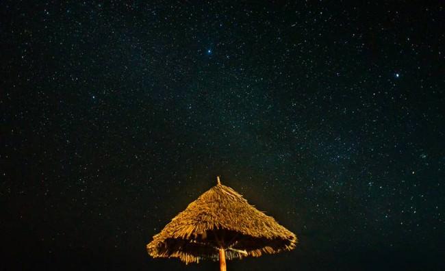 Ein Strohschirm vor dem Sternenhimmel