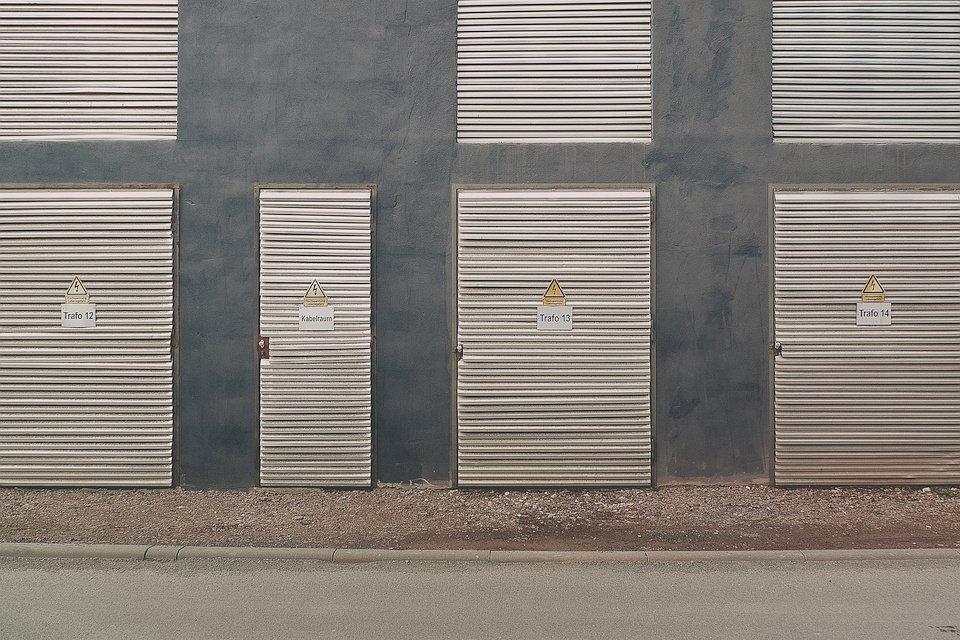Hausfassade mit Rolläden und Warnhinweisschildern.