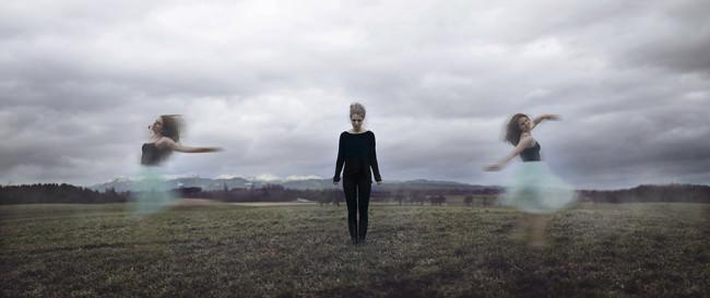 Eine Frau in Schwarz steht still, zwei andere tanzen um sie herum