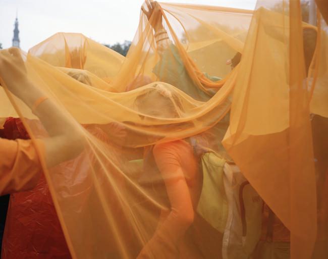 Menschen unter einem orangen Tuch