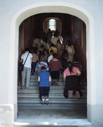 Menschen knieen auf einer Treppe.