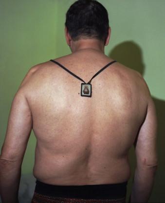 Ein Mann mit einem Amulett am Rücken.