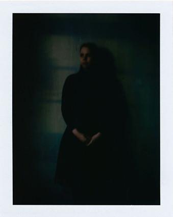 Eine Frau steht im Fensterkreuz und Abendlicht.