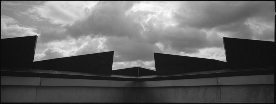 Gezacktes Dach vor bewölktem Himmel.