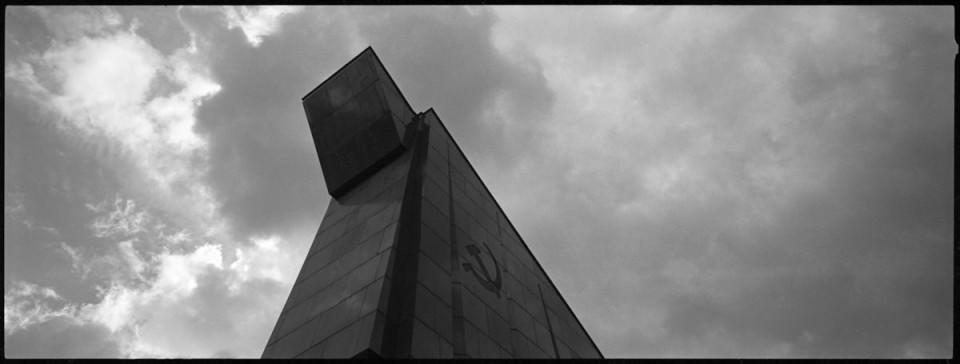 Vor dem Himmel aufragendes Bauwerk mit Hammer- und Sichel-Symbol.