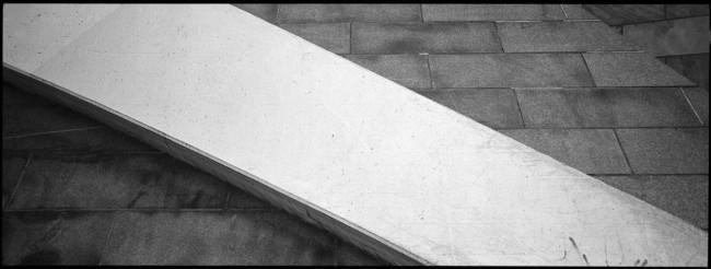 Diagonale aus hellem Beton vor dunkleren Betonplatten.